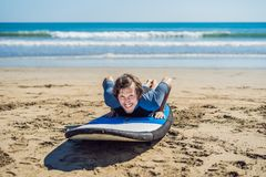 Young man surfer training before go to lineup on a sand beach. Learning to surf. Vacation concept. Summer holidays royalty free stock photography