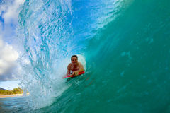 Young man surfing. Youthful young man Boogie Boarding Blue Wave royalty free stock photos