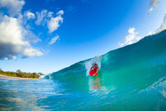 Young man surfing. Youthful young man Boogie Boarding Blue Wave royalty free stock image
