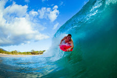 Young man surfing. Youthful young man Boogie Boarding Blue Wave royalty free stock photography