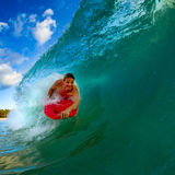 Young man surfing. Youthful young man Boogie Boarding Blue Wave stock photography