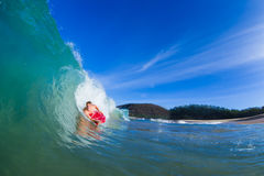 Young man surfing. Youthful young man Boogie Boarding Blue Wave Stock Photo