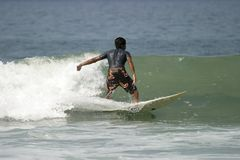 Young Man Surfing. A young man surfing a small wave with a nice curl in Mexico royalty free stock image