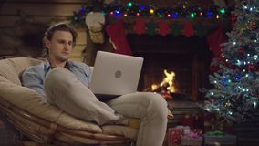 Young man surfing the Internet on a laptop in Christmas night. Sitting by fireplace in cosy puffchair stock video