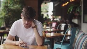 Young Man surfing internet in mobile phone, handy touch and sending text message in cafe. Handsome Teenager chatting in