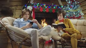 Young man surfing the Internet on smartphone while his mother reading book in Christmas night. By fireplace stock video footage