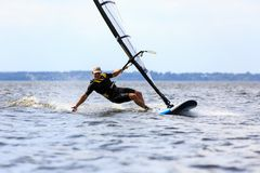 Young man surfing the wind in splashes of water. Young man surfing the wind and touching water surface with splashes Stock Images