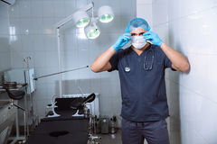 Young man surgeon takes on his protective glasses after operation in hospital. Young man surgeon takes on protective glasses after operation in hospital Royalty Free Stock Photos
