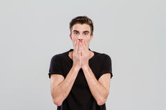 Young man surprised and closed mouth with hands Royalty Free Stock Photo