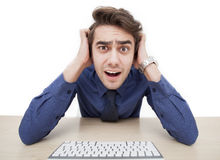 A young man is surprised while using a computer Stock Image