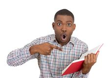 Young man surprised at what he reads Stock Photo