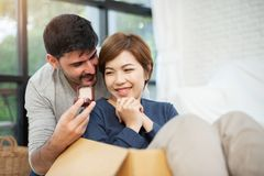 Young man surprising his beautiful girlfriend. Young men surprising his beautiful girlfriend with engagement ring in new moving house day royalty free stock photography