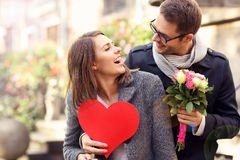 Young man surprising woman with flowers and heart. Picture of young men surprising women with flowers and heart Stock Images