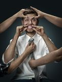 A young man surrounded by hands like his own thoughts royalty free stock images