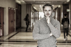 Young Man in Sweater Standing in School Hallway Royalty Free Stock Photo