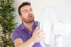 Young man suffering from summer heat and high humidity level. Young man sweating because summer heat haze Royalty Free Stock Photo
