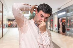 Man with sweating under armpit in shopping center. Young man with sweating under armpit in shopping center Stock Photos