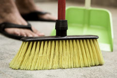 Young man sweeping the floor with a broom. Closeup of a young man sweeping the floor with a broom of green synthetic bristles and a green dustpan Stock Images