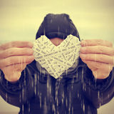Young man swhoing a heart under the rain, with a filter effect Royalty Free Stock Photography