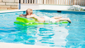 Young man is swimming with air mattress in pool Royalty Free Stock Photos