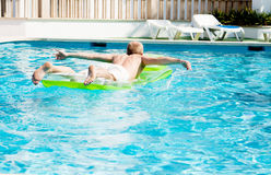 Young man is swimming with air mattress in pool Royalty Free Stock Photography
