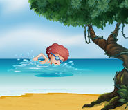 A young man swimming at the beach with an old tree Stock Image