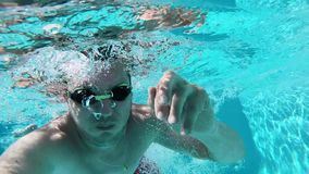 Young man swimming in blue clear pool. With sun rays reflections in the water stock video footage