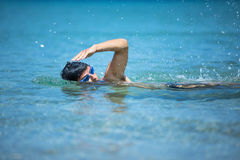 Young man swimming the front crawl in the sea Royalty Free Stock Image
