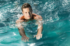 Young man swimming. An image of a handsome young man swimming in a pool Royalty Free Stock Photography