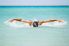 Young man swimming in oceans water. Dynamic and fit swimmer man swimming the butterfly stroke in ocean Stock Photos