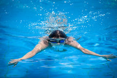 Young man swimming. In a pool Royalty Free Stock Photos