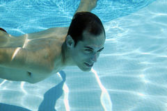 Young man swimming in pool. Young man diving in a swimming pool Royalty Free Stock Image