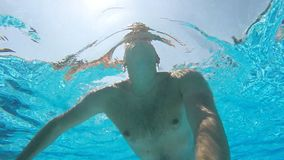 Young man swimming in pool and holding camera in hand. Underwater footage. Slow motion.  stock footage