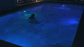 Young man in the Swimming Pool at Night stock video