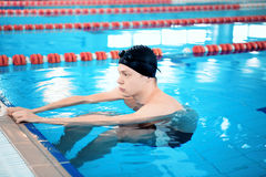 Young man in swimming pool. Refreshing exercise. Young handsome man with naked torso wearing a swimming cap warming up in the swimming pool Stock Photography