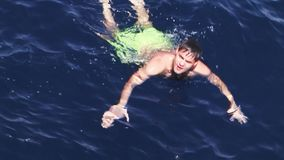 Young man swimming in sea. Party on yacht. Vacation. Sunny day. Blue water. stock footage