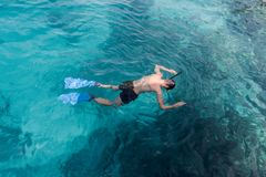 Young man swimming and snorkeling with mask and fins in clear blue water stock image