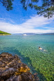 Young man swimming in stone beach with crystal clear tourquise s Stock Photography