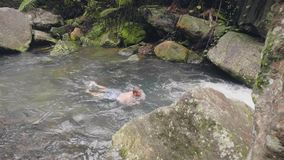 Young man swimming in stony river in tropical forest. Tourist man enjoying fresh water flowing in rainforest on stones stock video footage