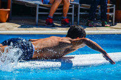 Young man swimming on surfboard in a pool Royalty Free Stock Images