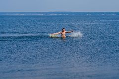 Young man swims in the water with the spray in summer on the beach Stock Image