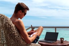 Young man in swimsuit working on a laptop in a tropical destination. Taking notes on a notebook stock photos