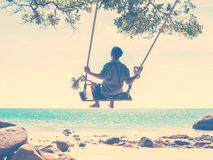 Young man swinging on the beach Stock Photography