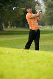 Young man swinging golf club Stock Images