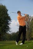 Young man swinging golf club Stock Photos