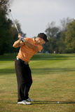 Young man swinging golf club Stock Image
