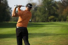 Young man swinging golf club, rear view Stock Images