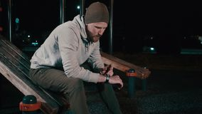 Man is sitting on sports ground in park at night and looking on smartwatch stock footage