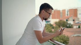 Young man is swiping on touch screen of mobile in balcony of flat in small city stock footage