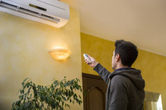 Young man switching on the air conditioner Royalty Free Stock Photo